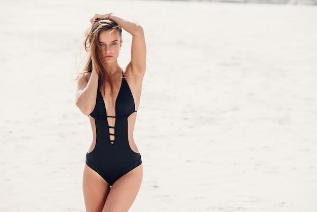 Sexy meisje met perfecte sportieve lichaam in zwarte zwembroek ontspannen op het strand. Premium Foto