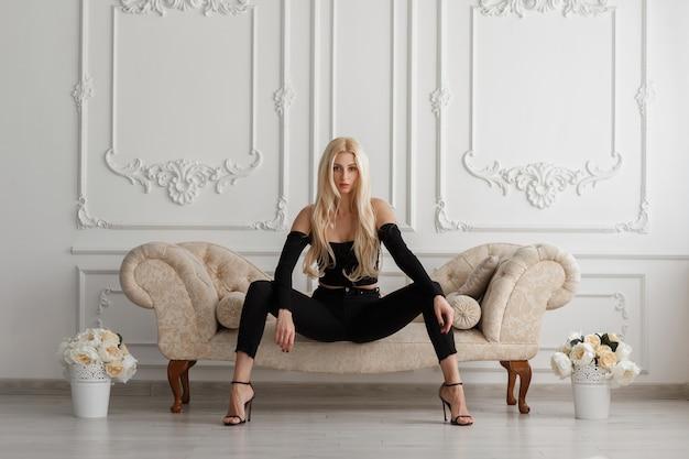 Sexy mooie jonge model vrouw in modieuze zwarte kleding met spijkerbroek zittend op een bank in een vintage kamer Premium Foto