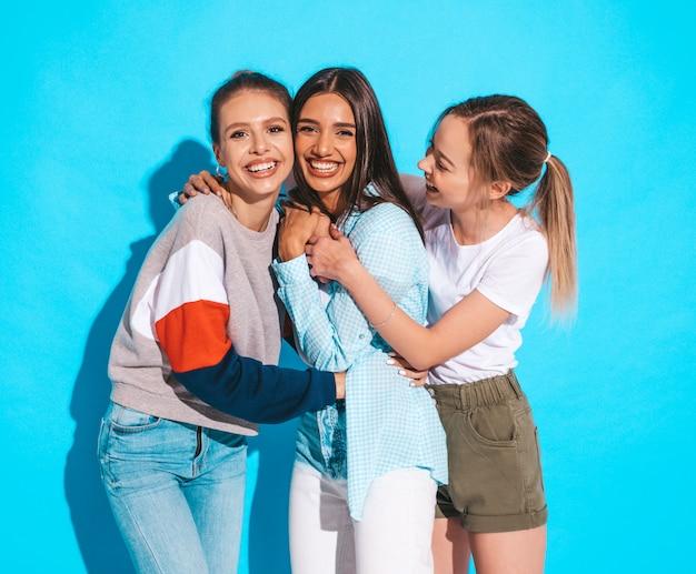 Sexy onbezorgde vrouwen die dichtbij blauwe muur in studio stellen. positieve modellen die plezier hebben en knuffelen Gratis Foto