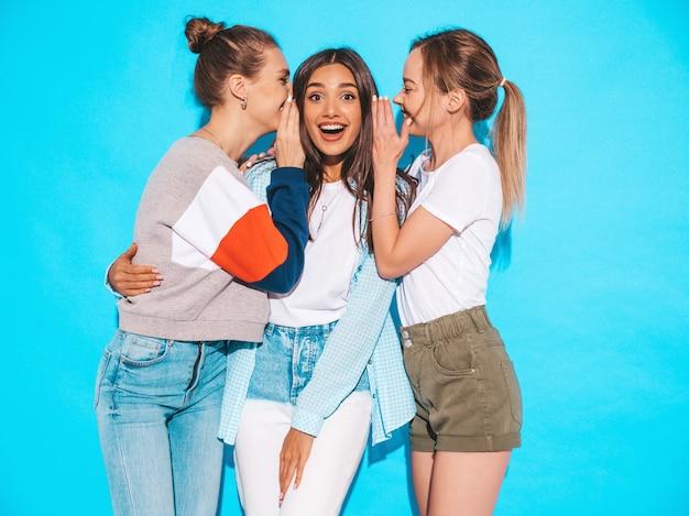 Sexy onbezorgde vrouwen die dichtbij blauwe muur in studio stellen. positieve modellen worden gek en hebben plezier. deel geheimen, roddels Gratis Foto