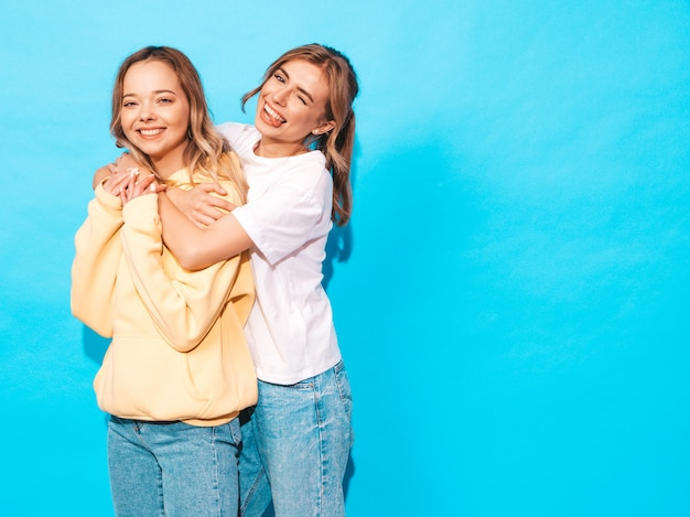 Sexy onbezorgde vrouwen die dichtbij blauwe muur stellen. positieve modellen met plezier en toont tong Gratis Foto