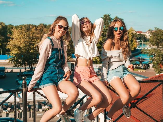 Sexy onbezorgde vrouwen die op leuning de straat zitten. positieve modellen die pret in zonnebril hebben Gratis Foto