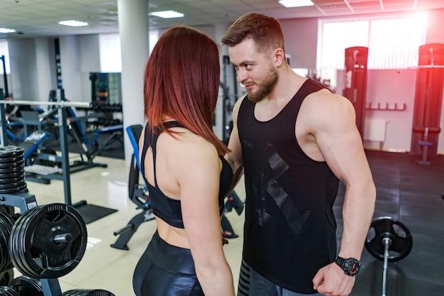 Sexy paar in sportkleding kijken elkaar in de sportschool. gespierde man en sportief meisje staan samen over de moderne sportschool. Premium Foto