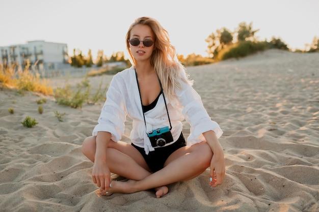Sexy reizende vrouw ontspannen op het strand in warme zomeravond. zittend op zand. witte blouse en zonnebril dragen. retro camera vasthouden. Gratis Foto