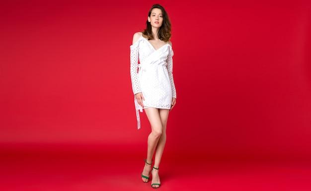 Sexy stijlvolle vrouw in zomer mode trend witte jurk poseren op rode studio Gratis Foto