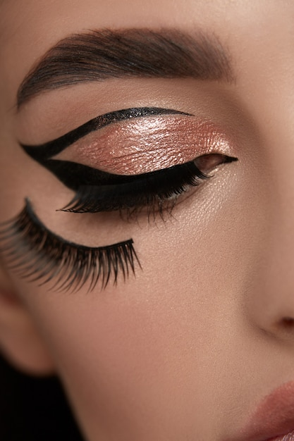 Sexy vrouw eyeliner met gouden schaduw en wimpers Premium Foto