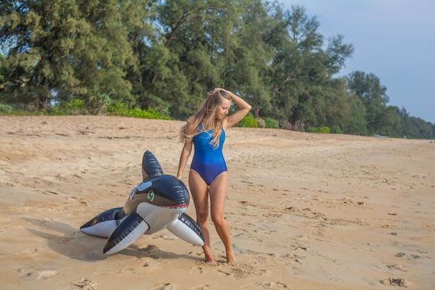 Sexy vrouw in blauw zwempak op het strand met opblaasbaar speelgoed Premium Foto