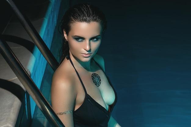 Sexy vrouw in het zwembad 's nachts Premium Foto