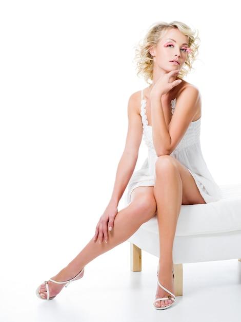 Sexy vrouw met mooie benen zit op witte stoel Gratis Foto