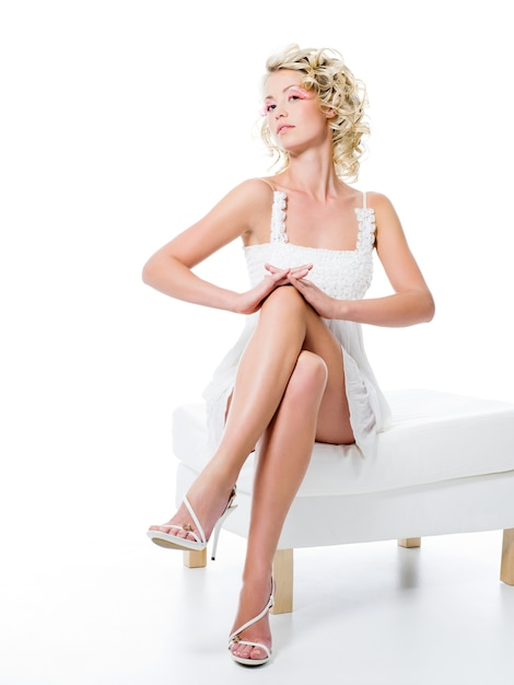 Sexy vrouw met schoonheid benen zit op witte stoel Gratis Foto
