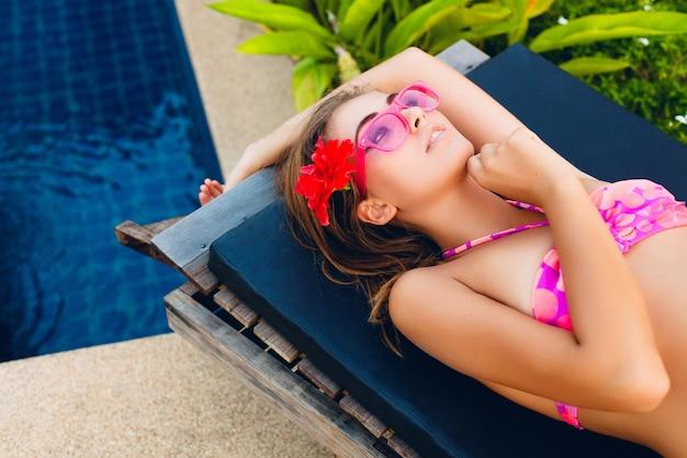 Sexy vrouw op zomervakantie liggend bij zwembad dragen van bikini en roze zonnebril, tropische bloemen, kleurrijke zomer mode-stijl Gratis Foto