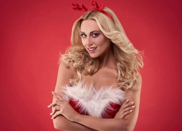 Sexy vrouwelijke kerstman op rode achtergrond Gratis Foto