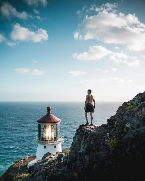 Shirtless fit man staande op een rotsachtige klif in de buurt van een vuurtoren baken en de zee Gratis Foto