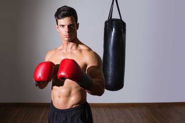 Shirtless gespierde bokser met bokszak in de sportschool Premium Foto