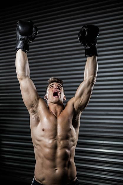 Shirtless mens met bokshandschoenen die bij de crossfitgymnastiek toejuichen Premium Foto