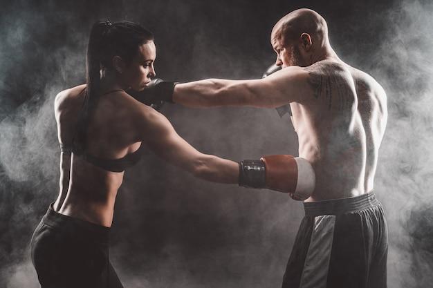 Shirtless vrouw die met trainer bij het in dozen doen en zelfverdedigingsles uitoefenen, studio, donkere achtergrond. vrouwelijke en mannelijke strijd. Premium Foto