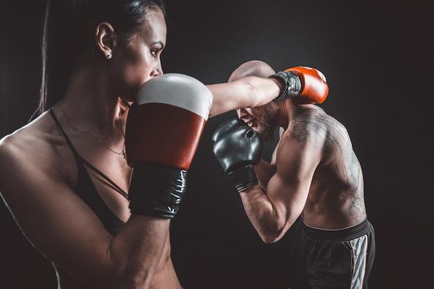 Shirtless vrouw oefenen met trainer op boksen en zelfverdediging les vrouwelijke en mannelijke strijd Premium Foto