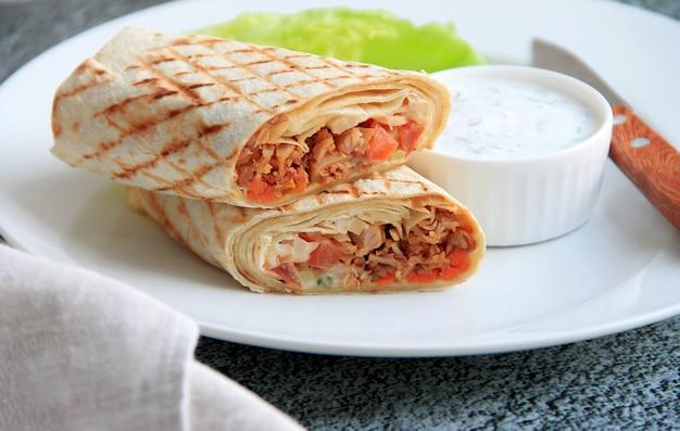 Shoarma met kip, groenten en kruiden op een witte plaat naast de saus en het mes Premium Foto