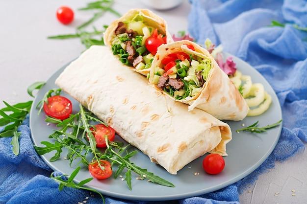 Shoarma van sappig rundvlees, sla, tomaten, komkommers, paprika en ui in pitabroodje. Premium Foto