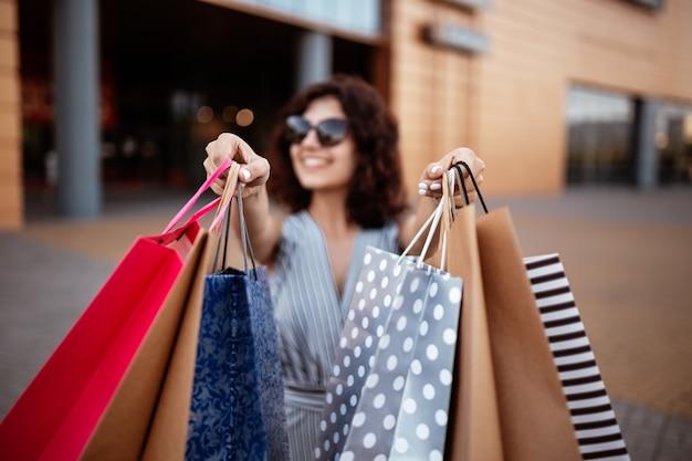 Shopaholic jonge mooie vrouw loopt het winkelcentrum uit met een pak tassen met aankopen. Premium Foto