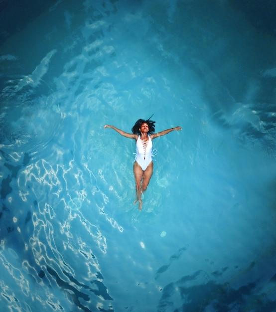 Shot van een afrikaanse vrouw in witte monokini zwemmen op watermassa Gratis Foto