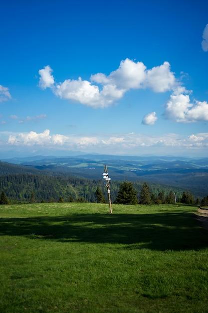Shot van een bord tegen een landschap van bomen en heuvels Gratis Foto