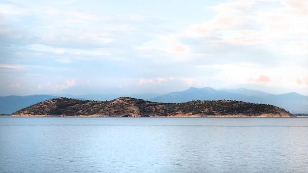 Shot van een eiland in de egeïsche zee met heuvels in griekenland Gratis Foto