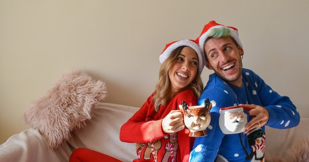 Shot van een gelukkig paar in kersthutten en kleding met grappige bekers Gratis Foto