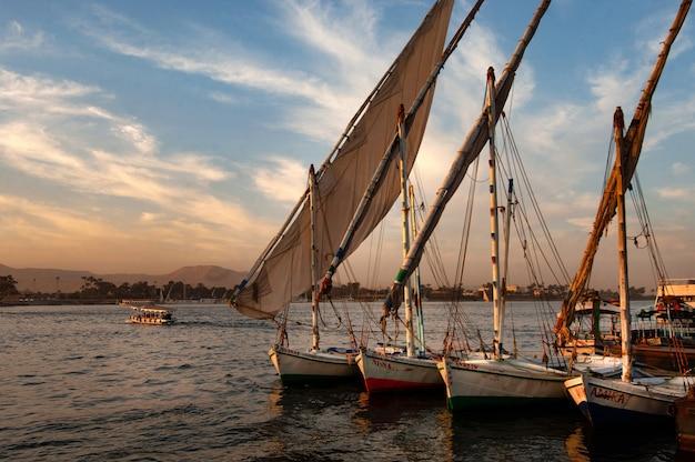 Shot van een groot aantal boten aangemeerd door de pier in rechte lijnen op zonsondergang Gratis Foto