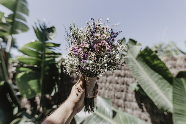 Shot van een persoon met een bruidsboeket en grote groene bladeren op de achtergrond Gratis Foto