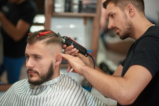 Shot van een professionele kapper op het werk. knappe jongeman krijgt een knipbeurt bij de plaatselijke kapperszaak. Gratis Foto
