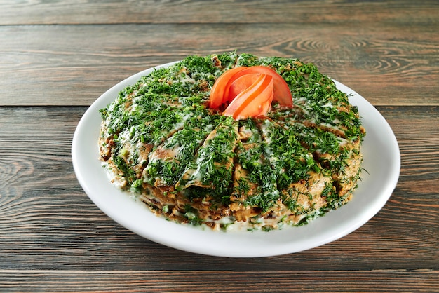 Shot van een stapel pannenkoeken gesneden en versierd met greens en tomaat bovenop geserveerd op de houten tafel in het restaurant eten heerlijke menu recept cusine koken eten. Gratis Foto