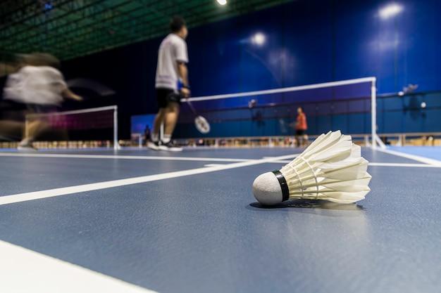 Shuttle pik badminton in het blauwe hof met het spelen van badminton. Premium Foto