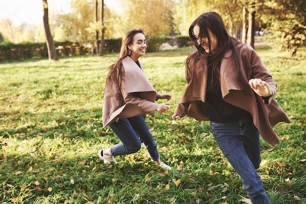 Side profiel van jonge lachende brunette tweeling meisjes met plezier, rennen en elkaar achtervolgen in herfst zonnig park op onscherpe achtergrond. Premium Foto