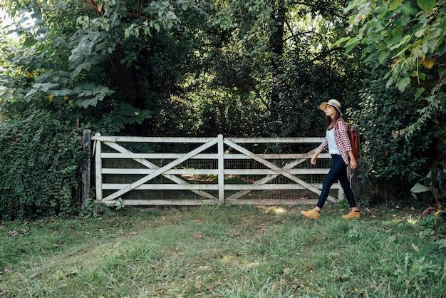Side shot van een vrouw langs een poort Gratis Foto