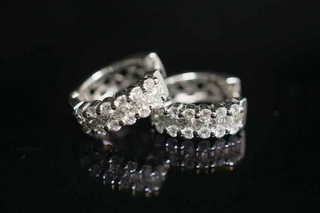 Sieraden diamanten oorbellen op zwart met reflectie Premium Foto