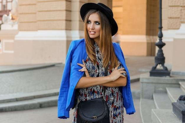 Sierlijk meisje in elegante herfst outfit wandelen tijdens vakantie in europa. stijlvolle leren tas. blauw jasje en zwarte hoed. Gratis Foto