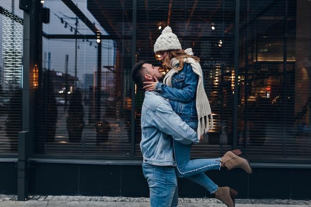 Sierlijk meisje in gebreide sjaal en hoge haklaarzen die pret hebben tijdens date. openluchtportret van europese kerel die zijn vriendin op stedelijke straat houdt. Gratis Foto