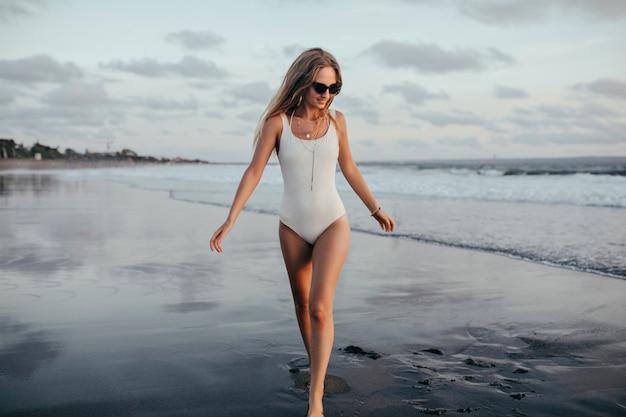 Sierlijk meisje kijkt naar zee met een glimlach terwijl ze rondloopt naast. openluchtportret van mooie jonge vrouw in badkleding die pret hebben bij wild strand. Gratis Foto