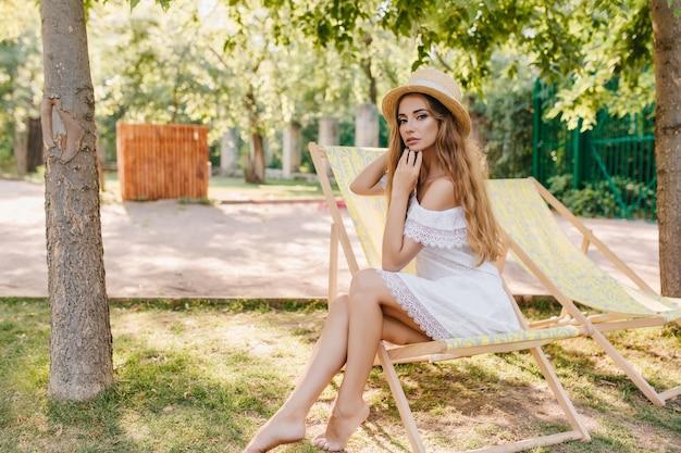 Sierlijke blootsvoets dame in strooien hoed zittend op chaise-longue met peinzende gezichtsuitdrukking. outdoor portret van vrij langharige meisje in witte jurk koelen op stoel in park. Gratis Foto