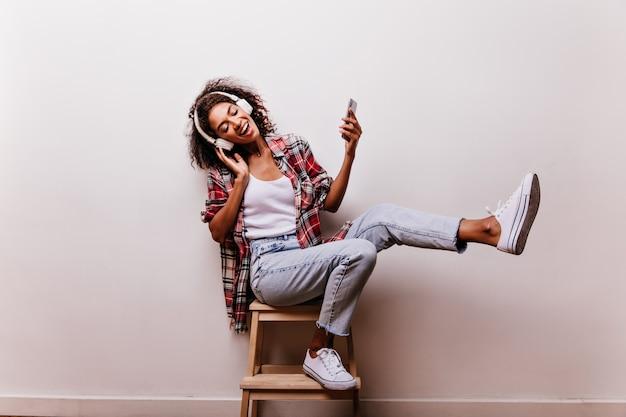 Sierlijke jonge vrouw in blauwe spijkerbroek muziek luisteren op wit. binnen schot van onbezorgd afrikaans meisje in hoofdtelefoons die met gesloten ogen glimlachen. Gratis Foto