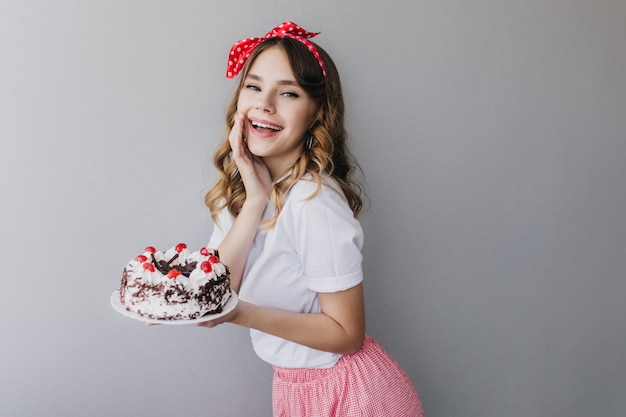 Sierlijke krullende witte dame die iets met aardbeientaart viert. portret van het glamoureuze feestvarken poseren met cake. Gratis Foto