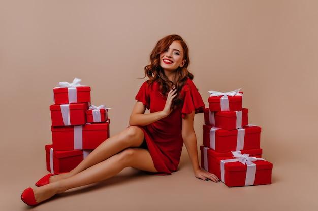 Sierlijke roodharige jonge vrouw koelen op nieuwjaarsfeest. tevreden gember meisje zit in de buurt van kerstcadeautjes. Gratis Foto