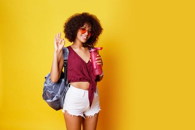 Sierlijke sport zwarte vrouw staande op geel en roze fles water dragen stijlvolle zomerkleding en rugzak. Gratis Foto