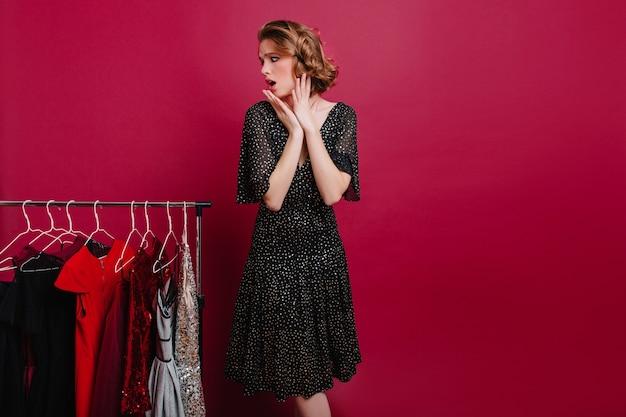 Sierlijke vrouw met bezorgde gezichtsuitdrukking outfit kiezen voor romantische date Gratis Foto