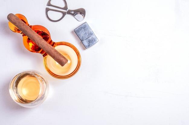 Sigaar, asbak, sigarettenschaar, witte betonnen tafel van lichter whiskyglas. Premium Foto