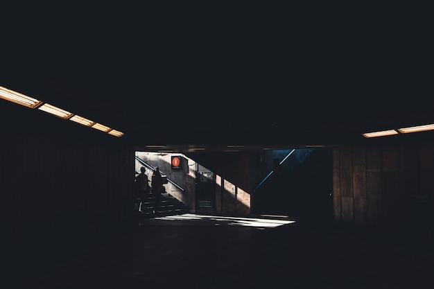 Silhoette van twee mensen die een donker schaduwrijk ondergronds gebouw binnengaan Gratis Foto