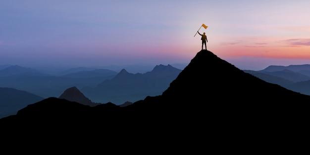 Silhouet die van zakenman zich op bergbovenkant bevinden over de achtergrond van de zonsondergangschemering met vlag, winnaar, succes en leidingsconcept Premium Foto