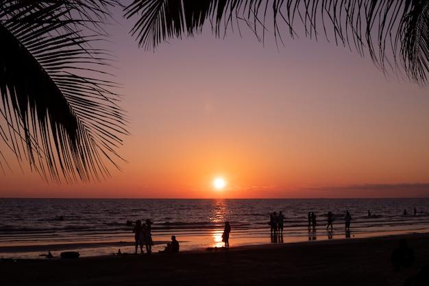 Silhouet kokosnoot verlaat frame met strand in avondlucht. Premium Foto