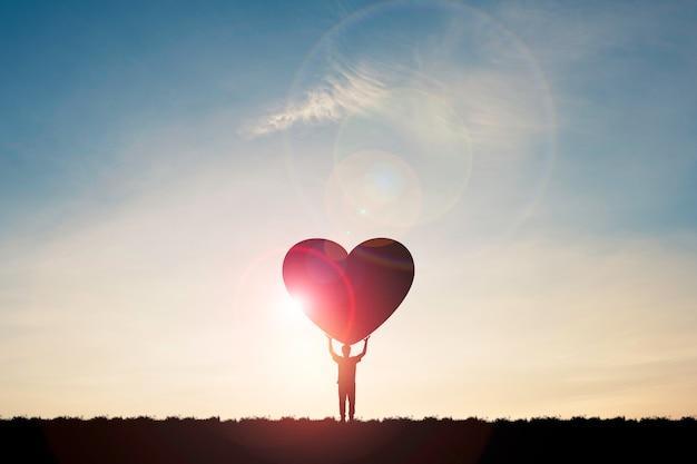 Silhouet man toont twee handen opstaan en hart met zonlicht en blauwe hemel, valentijnsdag concept dragen. Premium Foto